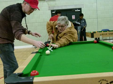 Two older participants playing snooker