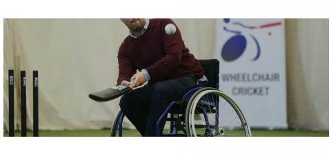 male wheelchair user hitting cricket ball with cricket bat