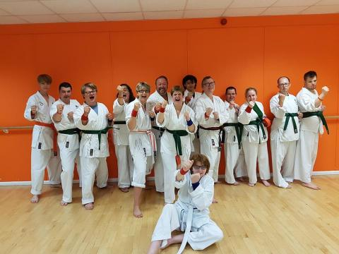 Group of disabled and non-disabled people laughing and wearing karate suits and their new green belts. One person is stting on the floor