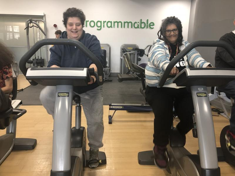2 members with disabilities using gym equipment