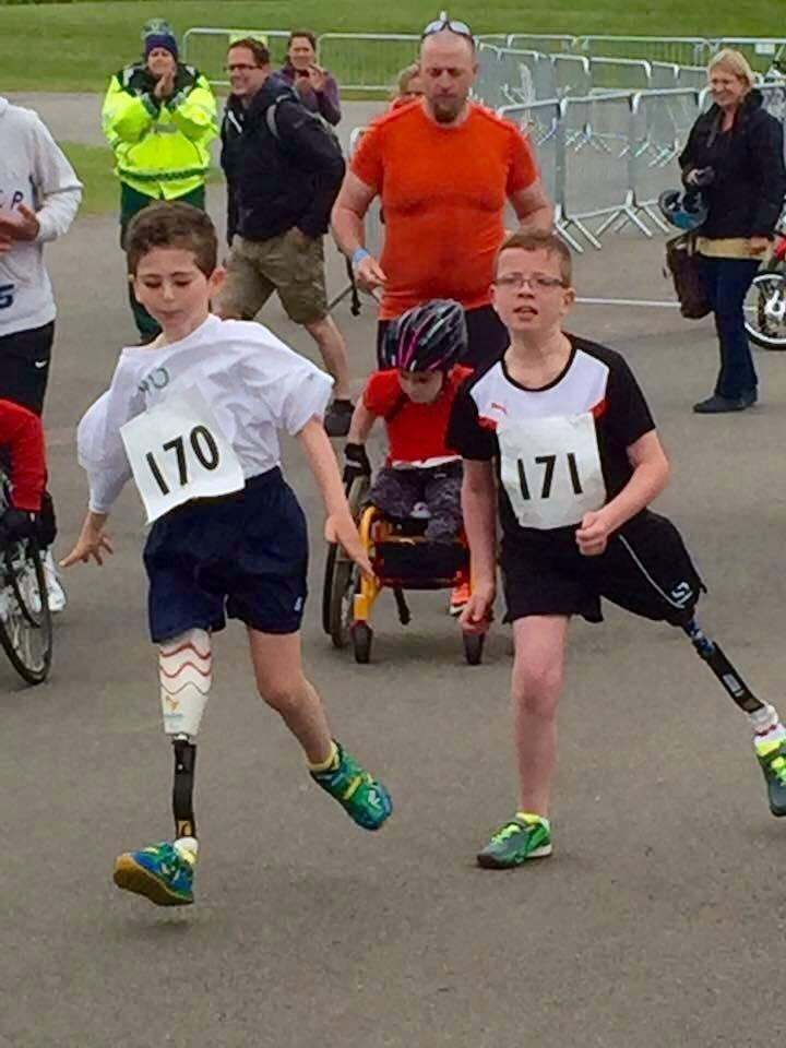 two boys with running blades running with race numbers on