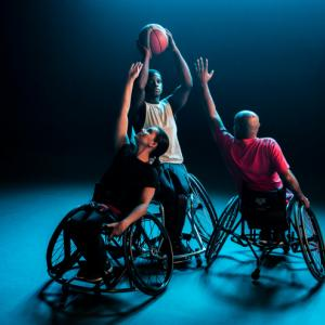 A wheelchair basketball player takes a shot while two others try to block him