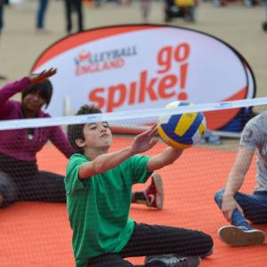young people playing sitting volleyball