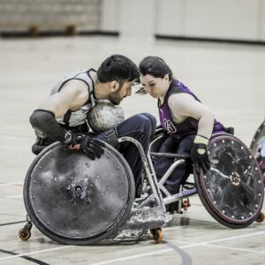 Two wheelchair rugby players face off